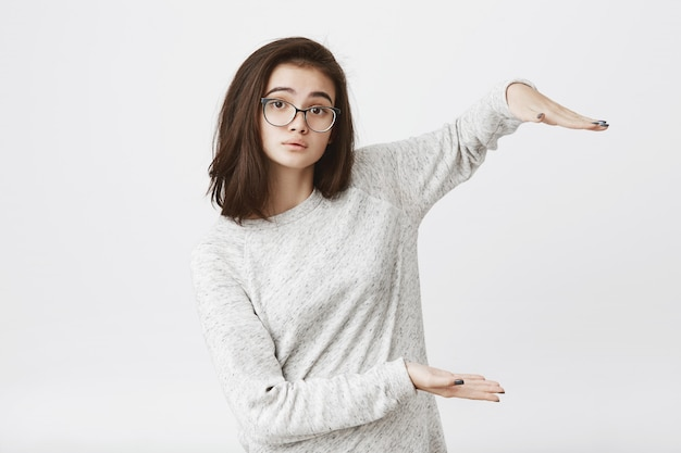 Cute attractive young model showing something with hands, wearing glasses and lifting eyebrows