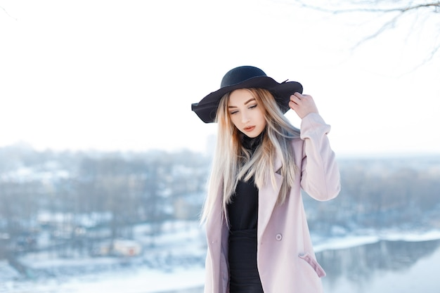 Cute attractive young woman in a chic black hat in a vintage elegant pink coat in a black knitted dress posing on the backdrop of a winter river on a sunny winter day. glamor blonde girl.