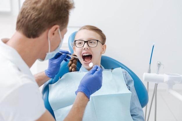 일반 검사를 위해 치과 의사를 정기적으로 방문하는 동안 입을 벌리고 앉아있는 귀여운 멋진 십대 소녀