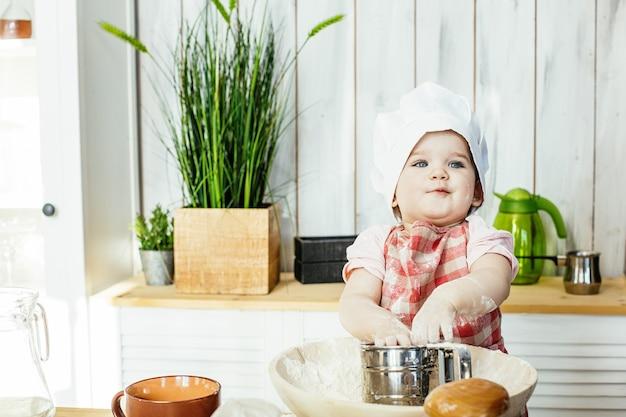 모자와 앞치마를 입은 귀여운 아기는 집에서 부엌에서 패스트리와 밀가루를 준비하는 행복하고 잘생긴