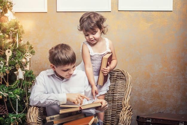 Симпатичные младенцы мальчик и девочка в кресле, читая книгу в рождественском ретро-интерьере