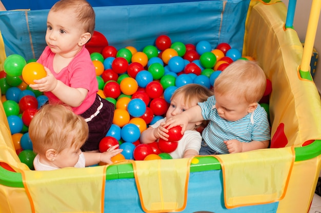 Cute babies playing with multicolored small balls inside the playpen