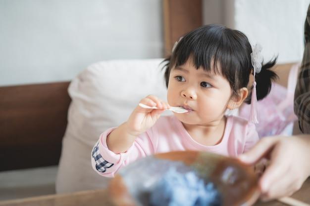 かわいい赤ちゃんとここで母親がカフェでアイスクリームを食べています