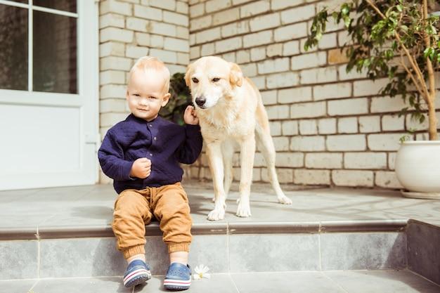Милый ребенок и добрая собака на крыльце дома