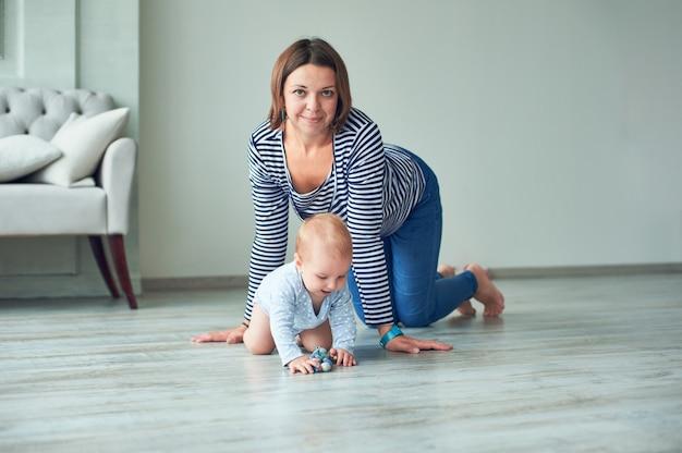 Милый ребенок и молодая мама ползут по дому