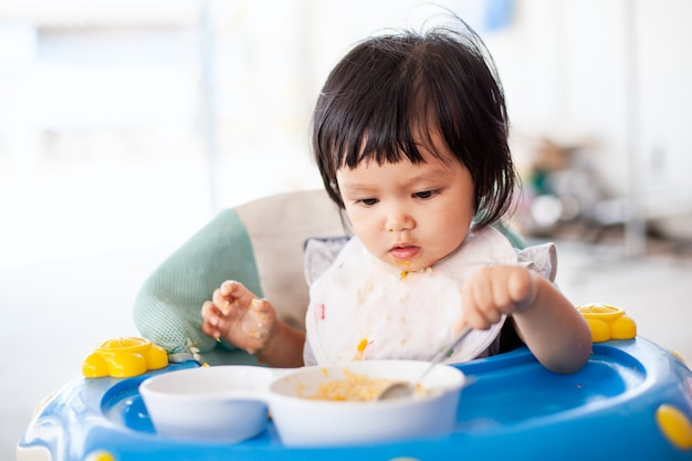 Cute baby asian child girl eating healthy food by herself and making a mess