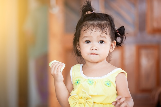 Cute baby asian child girl eating mango