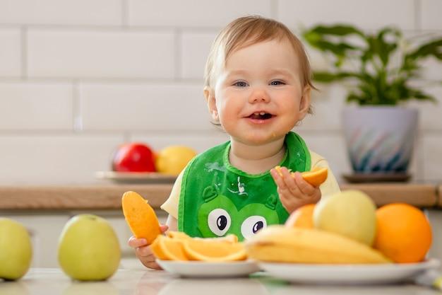 테이블에 귀여운 아기는 아침에 과일을 먹는다