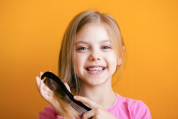 Cute baby, baby girl 6-8 years old combs her soft blond hair medium length comb and smiles on an orange wall