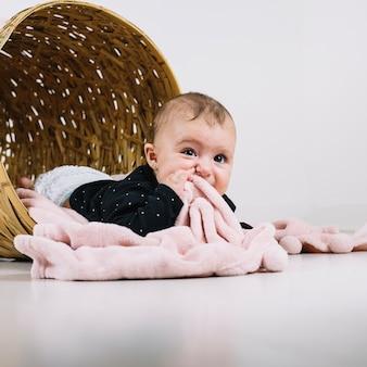 Cute baby in basket chewing blanket
