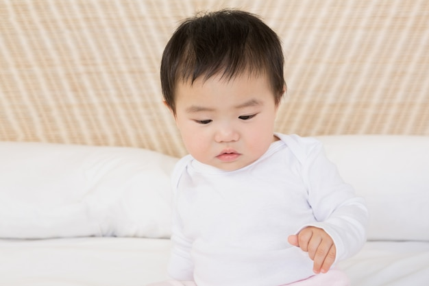 Cute baby on bed looking down
