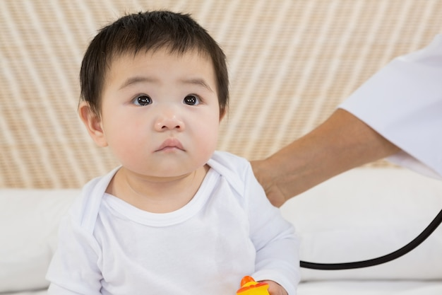 Cute baby being visited by doctor on the bed