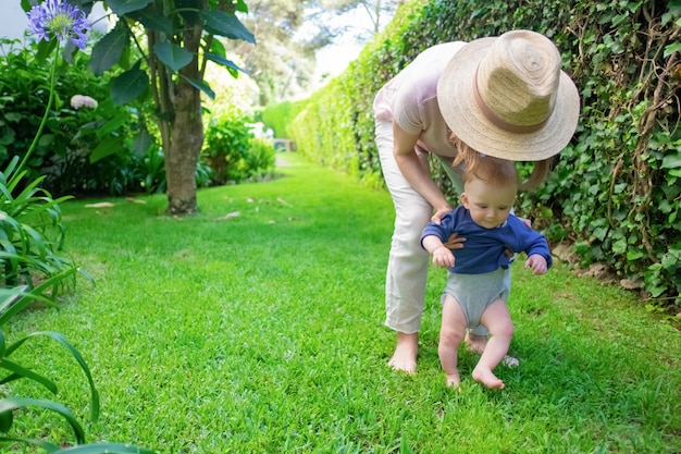 Bambino sveglio in camicia blu che fa i primi passi con l'aiuto della mamma e sorridente. giovane madre in cappello che tiene neonato sull'erba. primi passi a piedi nudi