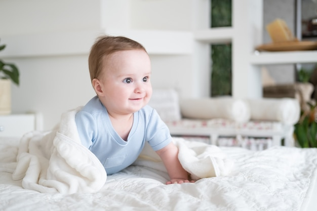 Cute baby boy 6 months old in blu bodysuit smiling and lying on bed with white plaid at home.