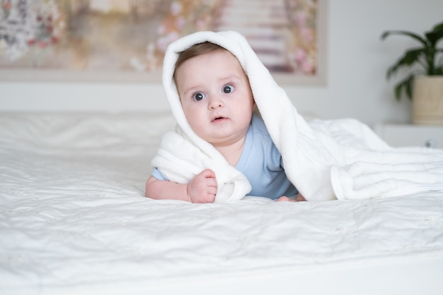 Cute baby boy 6 months old in blu bodysuit smiling and lying on bed with white plaid at home
