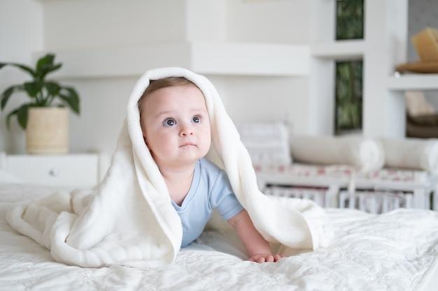 Милый мальчик 6 месяцев в синем боди улыбается и лежит на кровати с белым пледом дома