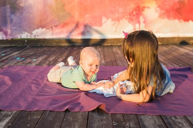 귀여운 아기와 어린 소녀는 담요에 누워.