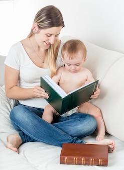 Милый мальчик и мать, глядя на фотографии в семейном альбоме