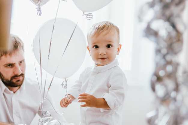 Cute baby boy celebrates his birthday one year at home in bright interior with his father