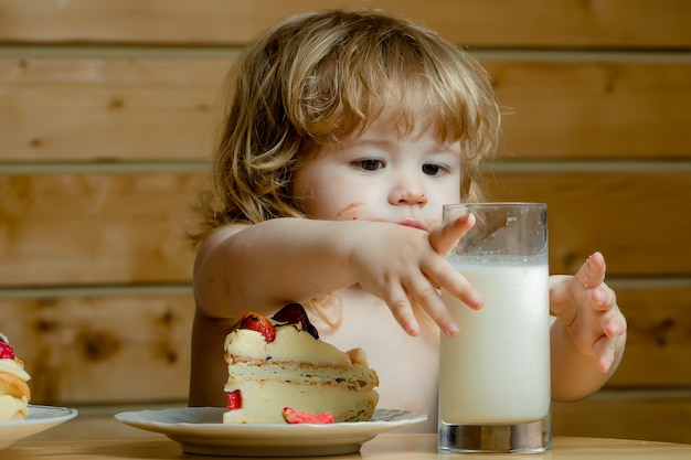 Cute baby boy child eating tasty pie or cake with red strawberry fruit and glass of yogurt