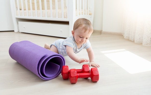 Cute baby boy crawling on floor and playing with dumbbells