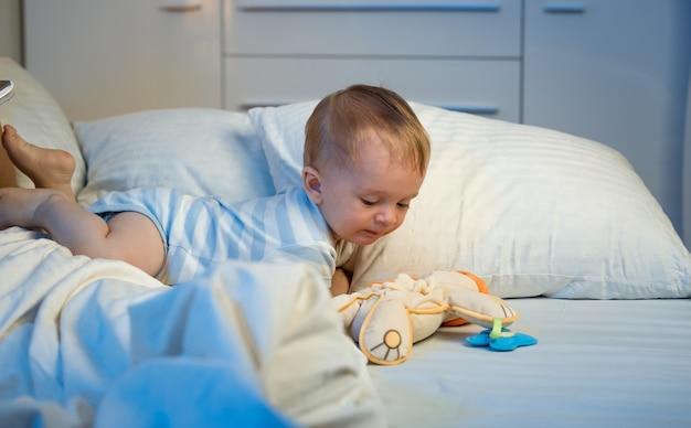 夜にベッドの上を這うかわいい男の子