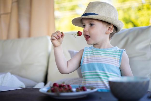 屋外の夏のテラスで新鮮な季節のベリーを食べるかわいい男の子イチゴとブルーベリー