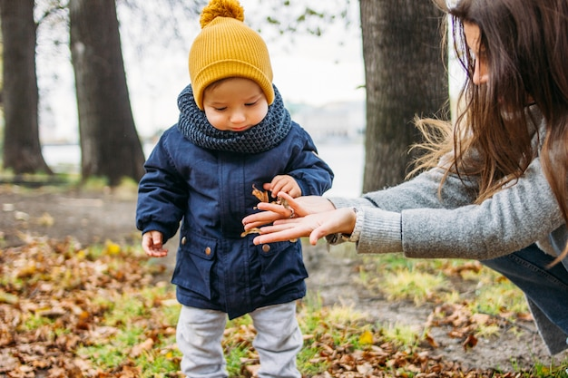 Cute baby boy in fashionable casual clothes explores world with mother in autumn nature park