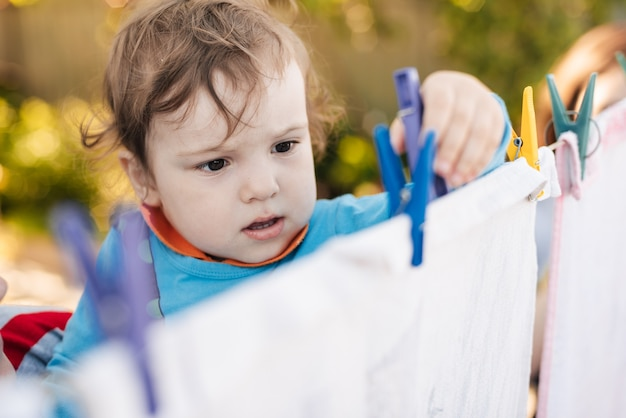 Cute baby boy helps hang laundry on a rope with clothespins