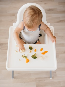 Cute baby boy in highchair eating vegetables alone