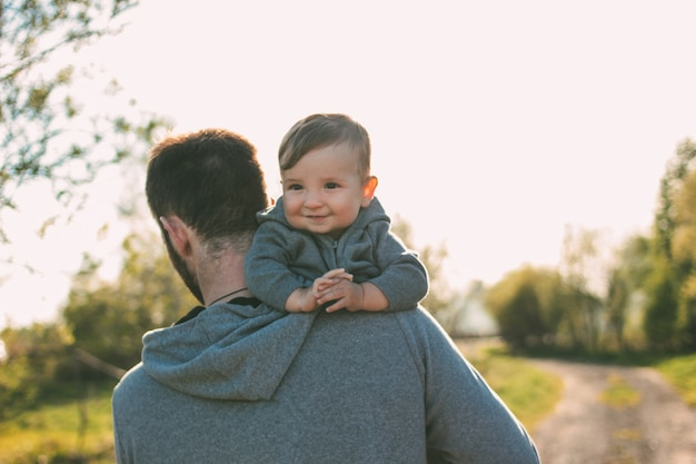 Cute baby boy on his dad shoulders walking on the road outdoors, sensitivity to nature concept
