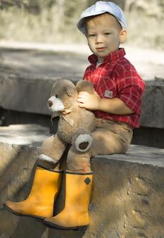 Милый мальчик в желтых резиновых сапогах весело проводит время, прыгает в лужах, спускает бумажный кораблик после весеннего дождя