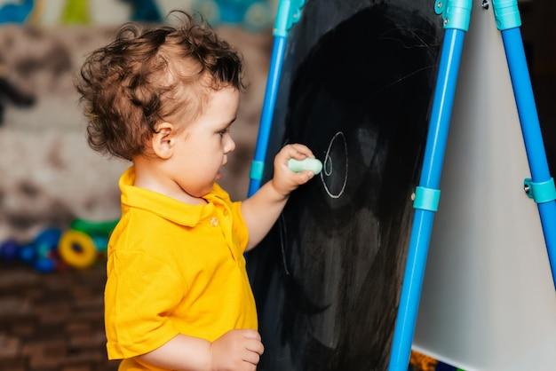 Cute baby boy learning to draw with chalk on a blackboard