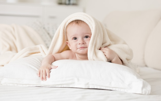 Cute baby boy lying on bed under towel after bathing
