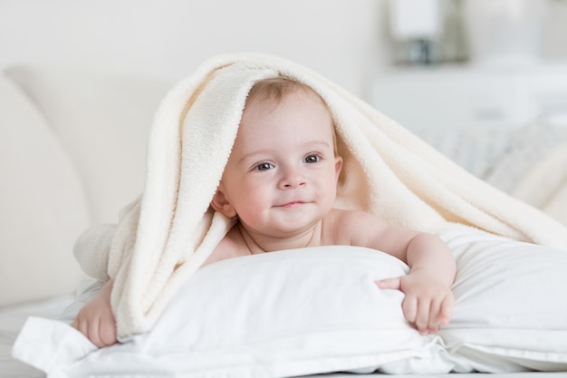 Cute baby boy lying under white blanket on bed
