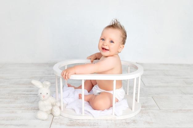 Милый мальчик на белом фоне с прической и большими голубыми глазами в подгузниках на белом фоне с прической, сидя в деревянной корзине