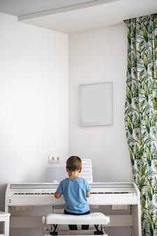 Милый мальчик играет на белом электрическом пианино форте, нажимая клавиши, ребенок учится в музыкальной школе