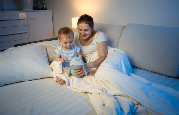 Cute baby boy playing with doll on bed with mother