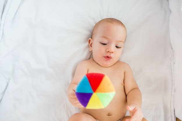Cute baby boy playing with a toy on a cradle
