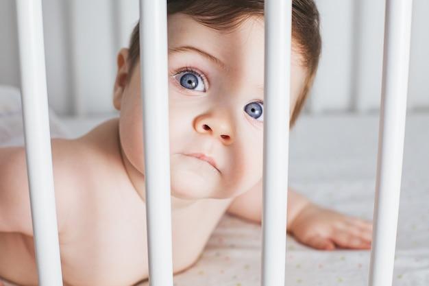 흰색 침대에 귀여운 아기 소년 초상화