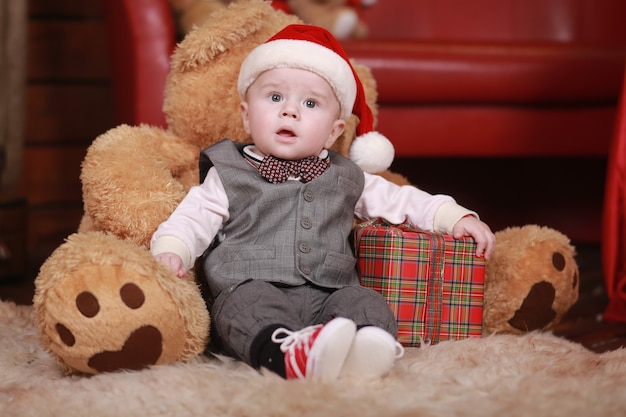 Cute baby boy in santa hat with big teddy bear and christmas gifts.