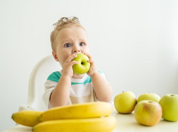 Милый ребенок мальчик сидит за столом в детском кресле ест яблоко на белой кухне