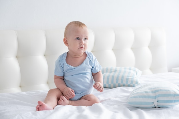 Cute baby boy sitting in the bed at home. bedding for children.