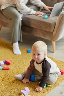 Cute baby boy sitting on the floor and playing with colorful blocks in the room