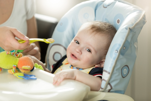 Cute baby boy sitting in highchair and looking at camera