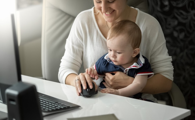 母親の膝の上に座って、コンピューターのマウスで遊ぶかわいい男の子