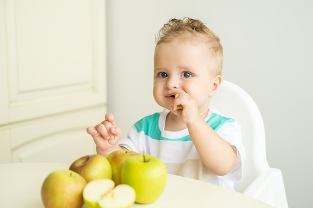 Cute baby boy sitting sitting at the table in child chair eating apple on white kitchen.