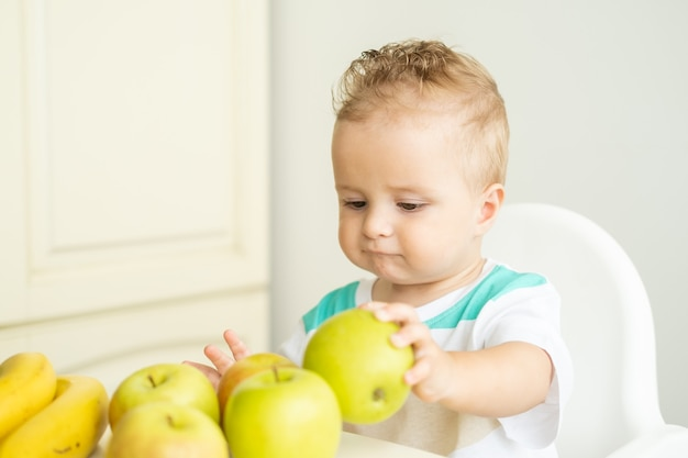 Cute baby boy sitting at the table in child chair eating apple on white kitchen.
