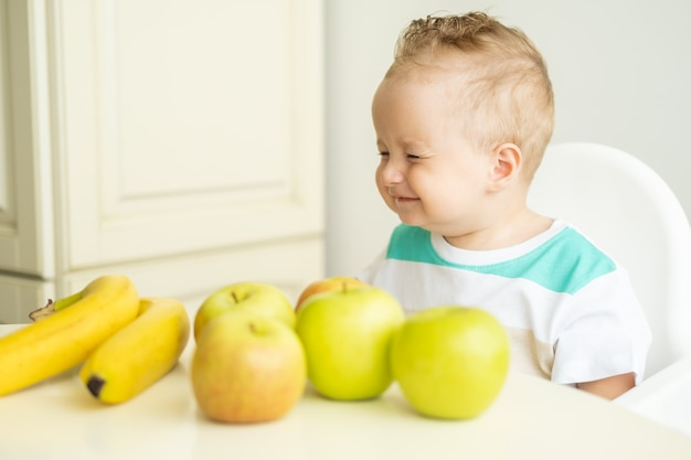 Cute baby boy sitting at the table in child chair eating apple on white kitchen