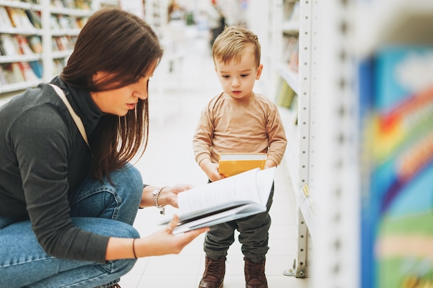 Cute baby boy toddler child in bookstore with his mother with open book